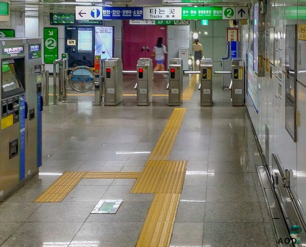 U-Bahnstation, links Fahrkartenautomaten, geradeaus Eingang zum Schienenbereich, darüber Schilder und Wegweiser in den entsprechenden Farben der Linien. Gelbe Linien am Boden sind zur Orientierung für blinde Fahrgäste.