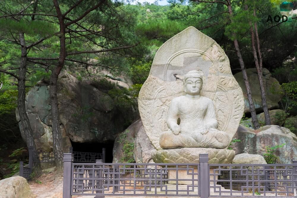 Buddhafigur mit einer kleinen Höhle. Die soll als Schlafplatz von einem Mönch genutzt worden sein.