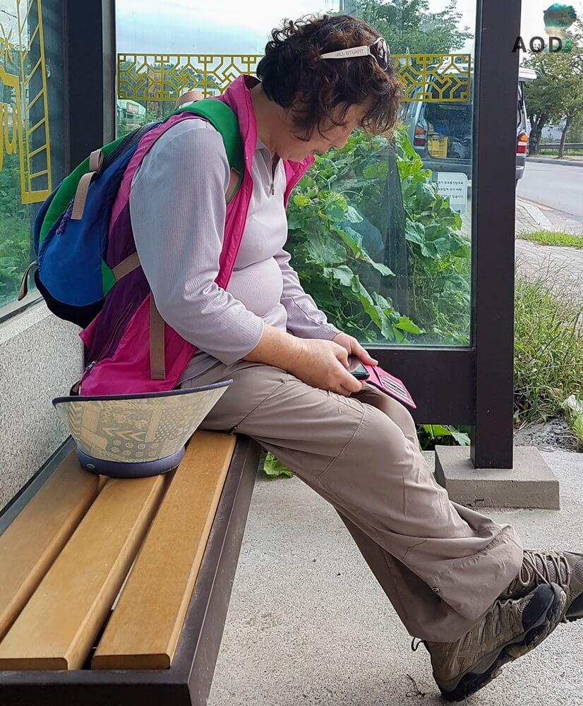 Meine Begleiterin wartet mit mir an der Bushaltestelle zund schaut nach dem nächsten Bus.